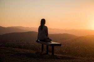 Image of woman facing sun and meditating